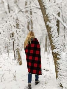 girl walking in snowy woods